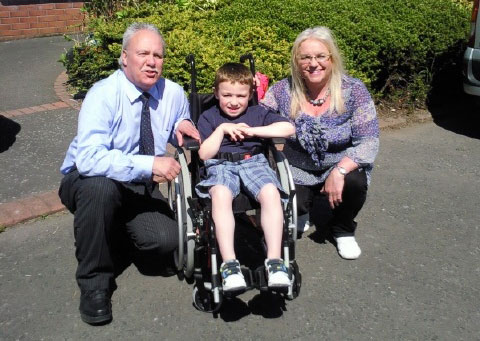 Gerry and Geraldine presenting JAmie with his new wheelchair